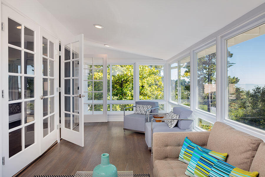 A nicely decorated sunroom overlooking a backyard